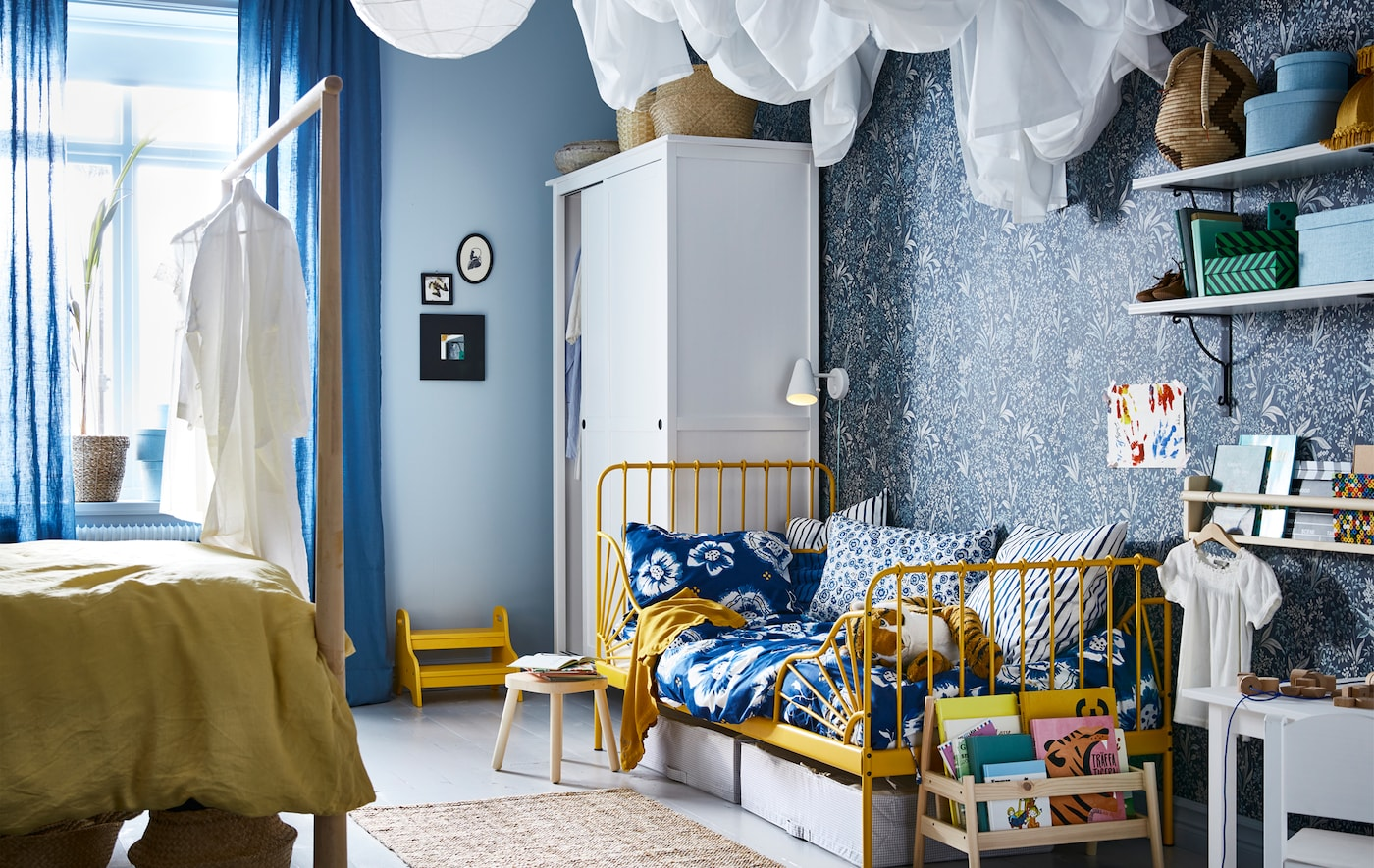 A bedroom with blue and yellow colour scheme, with an adult bed on one side and child's bed on the other side.