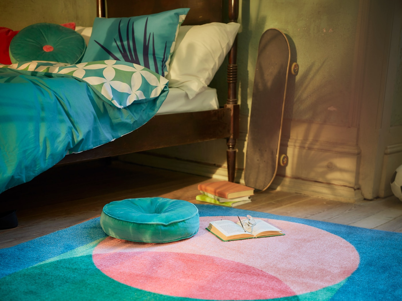 A bedroom with GRACIÖS textile series in turquoise tones including a quilt cover, patterned rug and a round velvet cushion.