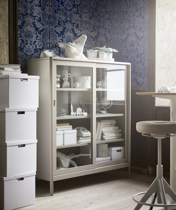 A beige glass-fronted cabinet in the corner of an office space with blue patterned wallpaper.