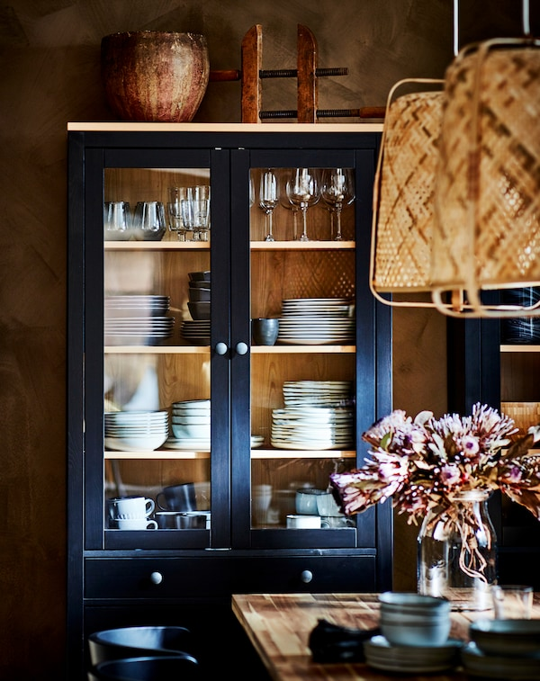 A black-brown HEMNES glass-door cabinet displaying dinnerware, standing behind a dinner table with a flower vase.