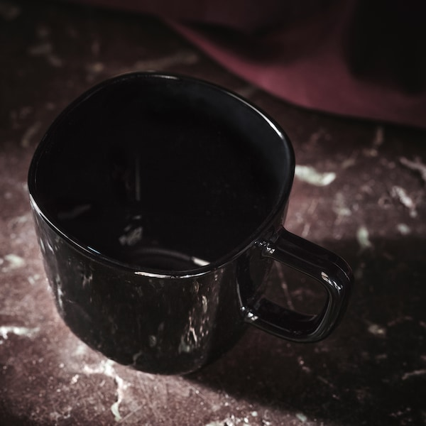 A black glossy BACKIG mug with a handle placed on a dark-red stone marble surface with some fabric in the background.