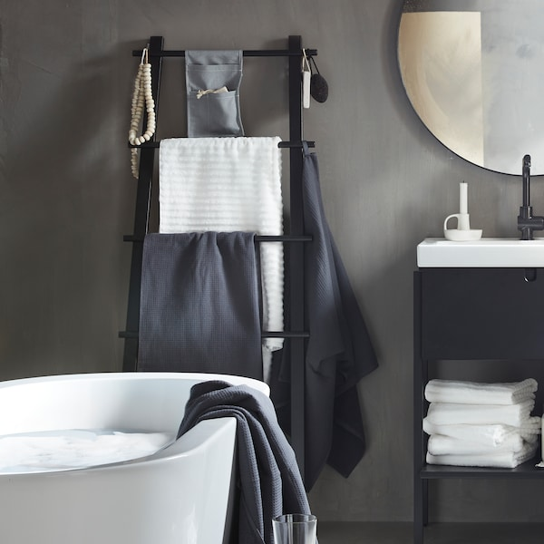 A black ladder-like VILTO towel stand in wood leaning against the grey wall of a minimalistic bathroom.