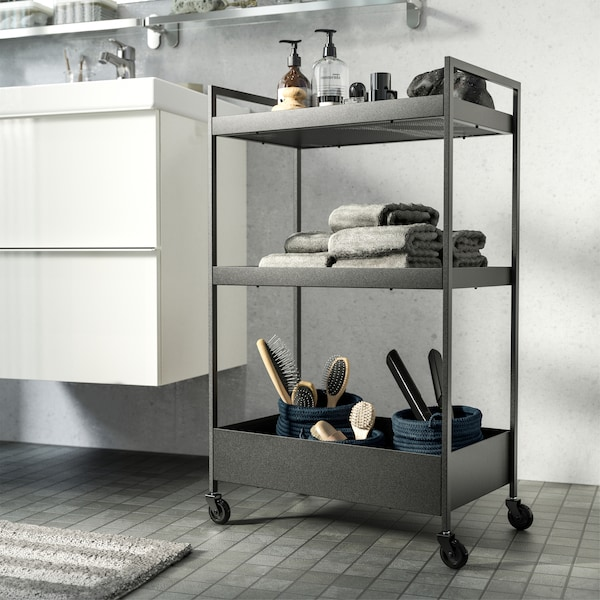 A black trolley in a white/grey bathroom. It stores soap, towels and brushes and stands next to the wash basin.