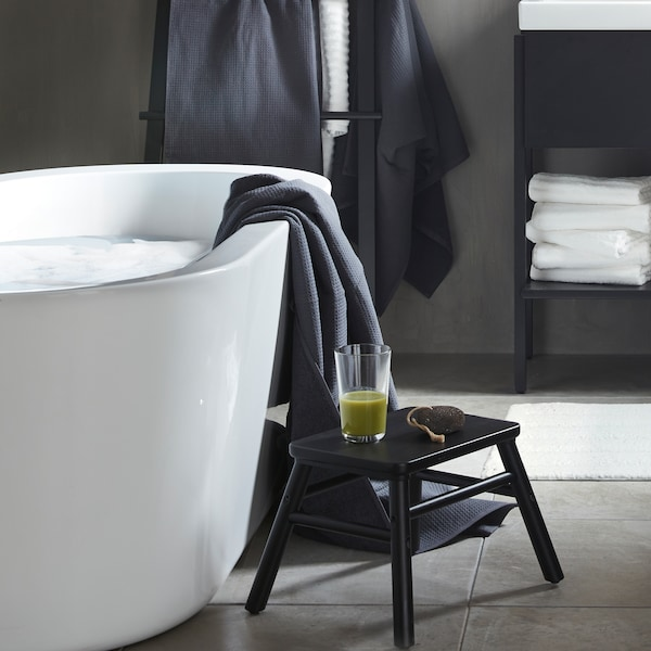 A black VILTO step stool in wood placed beside a bathtub with a glass of green smoothie on it in a minimalistic bathroom.