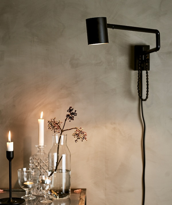 A black wall light on a painted grey wall, shining light on a glass counter with a mix of glassware, candles and tealights.