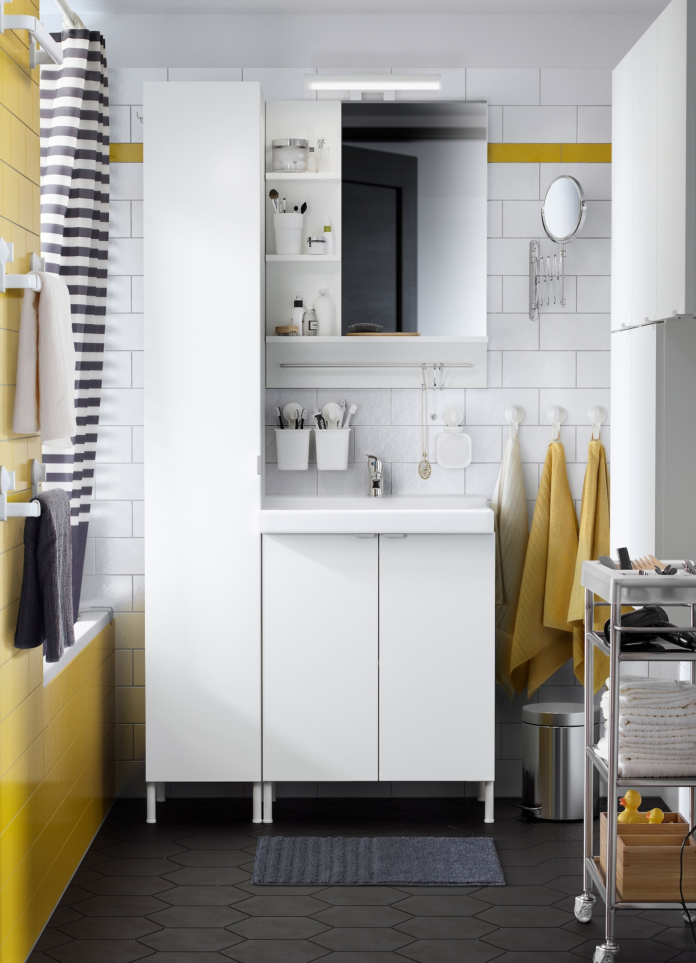 A black, white and yellow bathroom with LILLÅNGEN/TALLEVIK washbasin cabinet in white with 2 doors and a LILLÅNGEN wall cabinet and LILLÅNGEN high cabinet in white providing plenty of storage space and an organised look and feel.