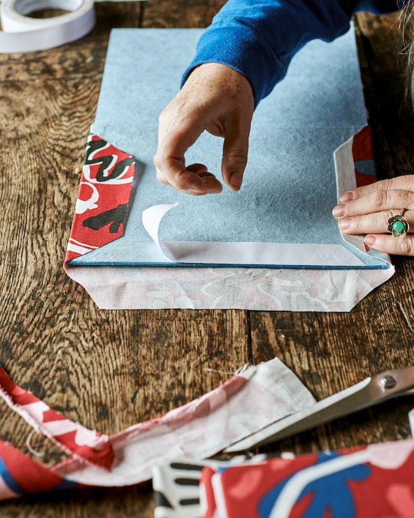A blue notebook open on the cover page, hands stick double-sided tape to the edge, preparing to attach red patterned fabric.