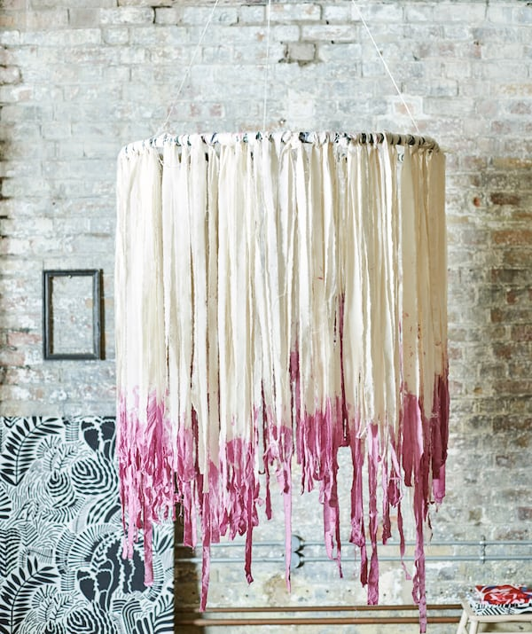 A boho mobile hangs by a brick wall. The hoop is decorated with tassel-like strips of white fabric, dyed pink at the ends.