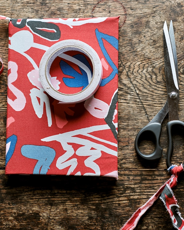 A book covered in red patterned fabric on a rustic wood table with a roll of sticky tape on top, next to a pair of scissors.