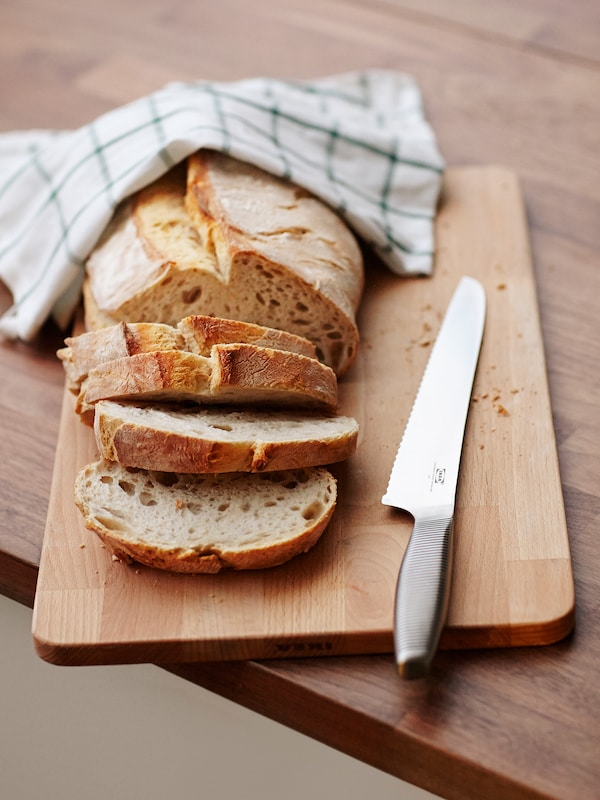 A bread knife on a wooden chopping board next to a loaf of bread where some slices have been cut and a tea towel.