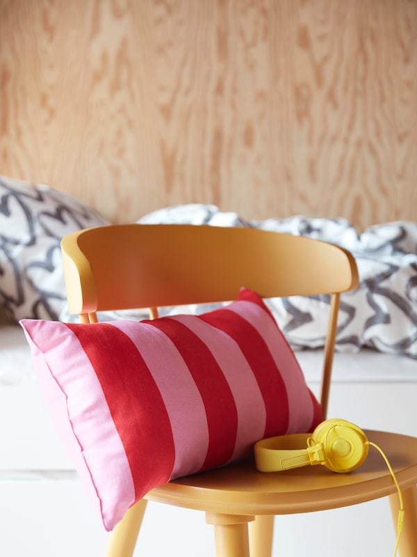 A bright pink and red striped cushion sits on top of a vibrant yellow children's chair, with matching yellow headphones.
