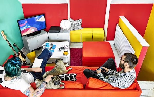 A brightly coloured room with sofa and games console.
