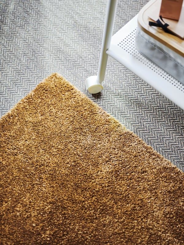 A brown-yellow STOENSE rug is placed on a grey floor, with a white metal rolling table alongside it.