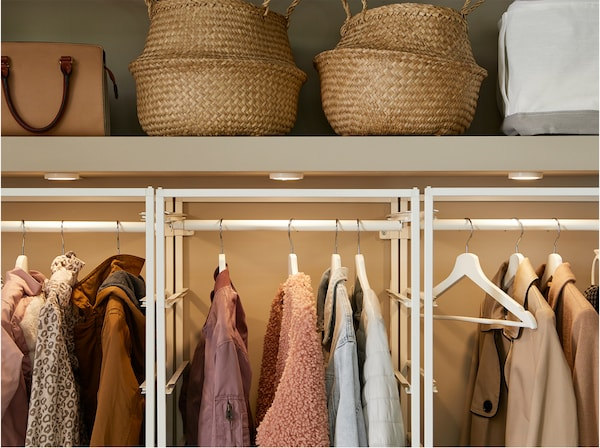 A built-in closet with JONAXEL white storage system inside with clothes rails, lighting and baskets in seagrass.