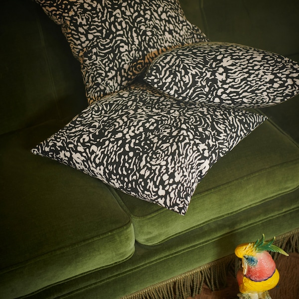 A bunch of GRIMHILD cushion covers featuring an abstract black and natural pattern placed in a green velvet sofa.
