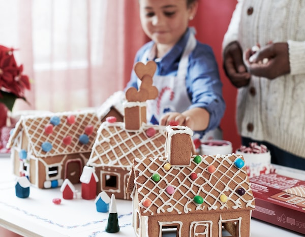 A child building three VINTERSAGA model houses made of baked gingerbread dough and decorated with icing and sweets.