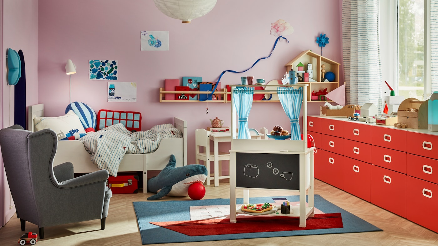 A children's room with a SPISIG play kitchen with curtains, a STRANDMON children's armchair and a SUNDVIK extendable bed.