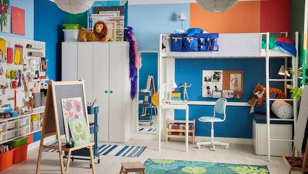 A children's room with a white VITVAL loft bed with a built-in desk underneath, a MÅLA easel and lots of different storage.