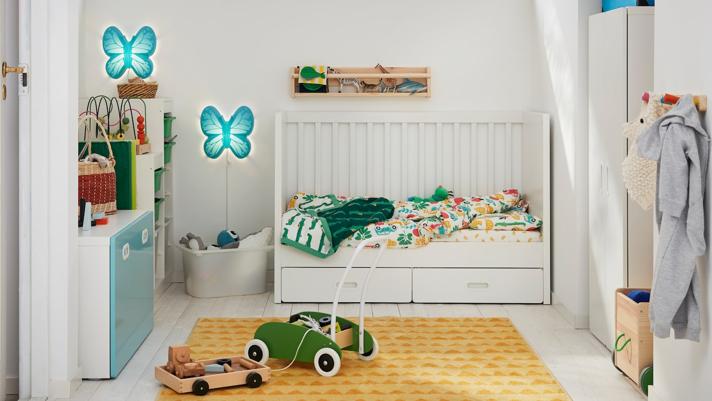 A child's bedroom with a STUVA/FRITIDS cot with one side removed and a green MULA toddle truck on a RÖRANDE rug.