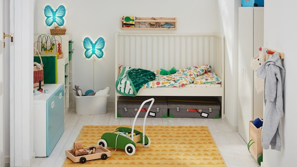 A child's bedroom with a white GULLIVER cot with one side removed and a green MULA toddle truck on a RÖRANDE rug.