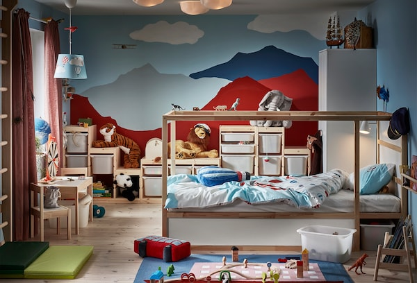 A child's room visually dominated by a back wall with painted mountains. Reversible bed, wall bars, toys, various storage.