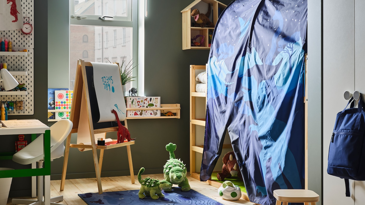 A child's room with a KURA reversible bed with a KURA bed tent and lots of toy dinosaurs. A MÅLA easel is near the bed.