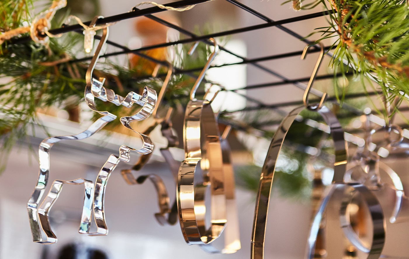 A close-up image of a wire trellis hung above a kitchen island, decorated with greenery and cookie cutters.