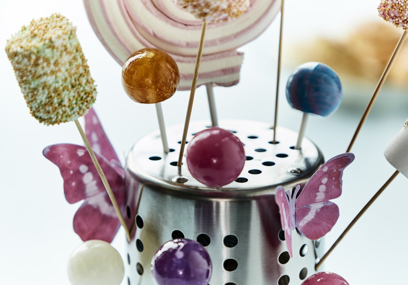 A close-up image of an IKEA ORDNING utensil holder turned upsed down and used as a holder for lollipops.