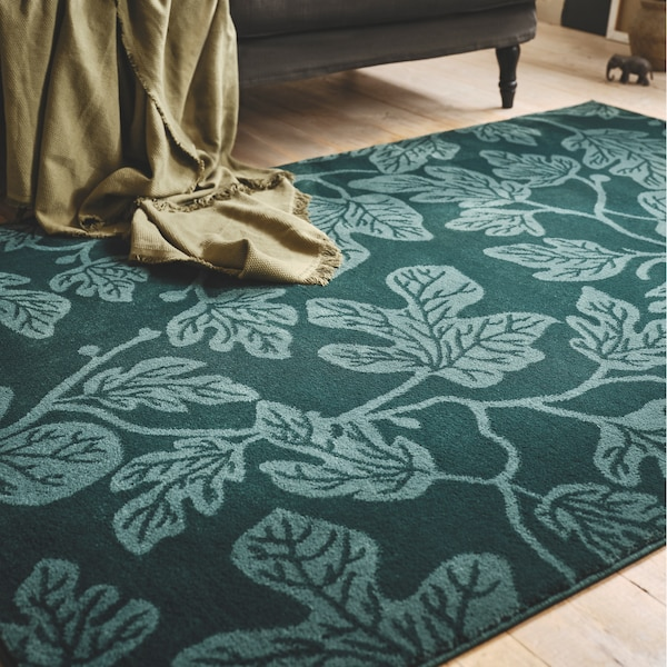 A close-up of a dark green HILDIGARD rug with a fig leaf pattern, a sofa and olive throw can be seen on the side.