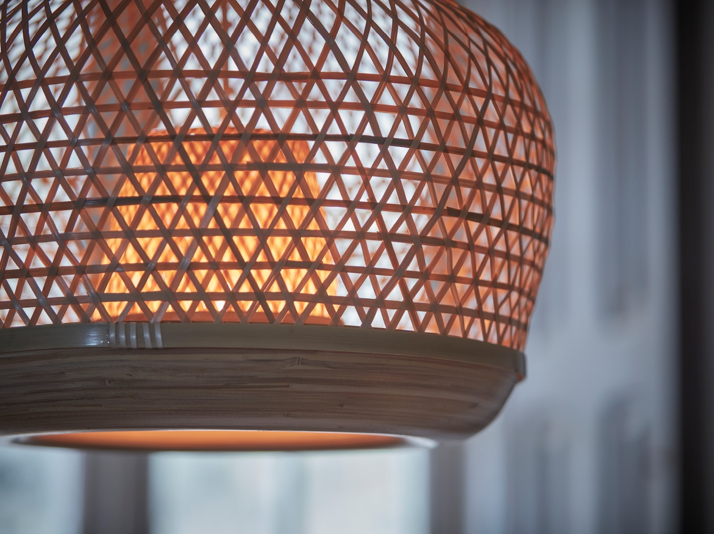A close-up of a switched on MISTERHULT pendant lamp handwoven in the light, natural material bamboo.