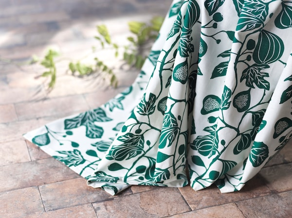 A close-up of ALPKLÖVER curtains featuring a winding pattern of fig leaves in white and green reaching to the floor.