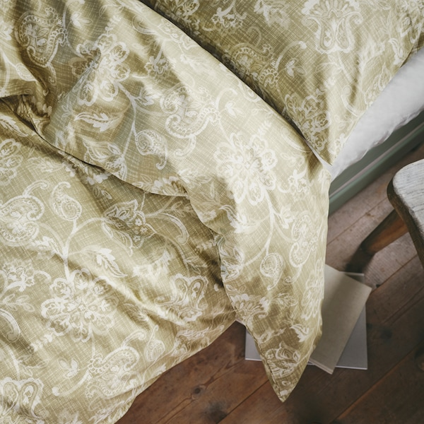 A close-up of an olive-green JUNIMAGNOLIA quilt cover and pillowcase featuring a traditional floral pattern.