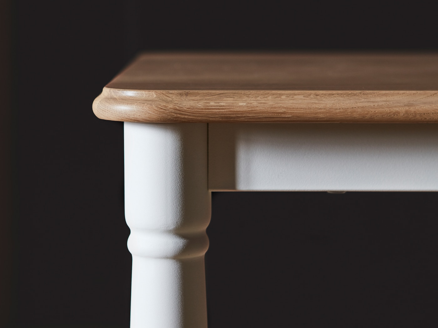 A close-up of DANDERYD dining table with an oak veneer table top and white legs shaped in a traditional style.