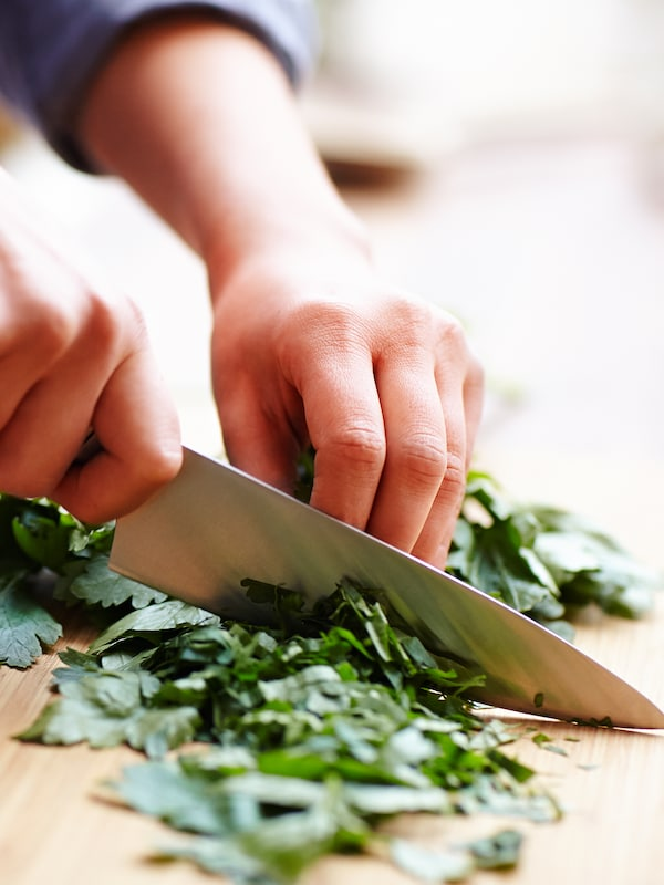 A close-up of hands chopping green leaves with a kitchen knife.