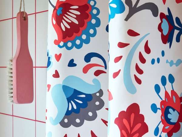 A close-up of KRATTEN shower curtain featuring a traditional Scandinavian, floral pattern in many colours.