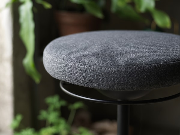 A close-up of LIDKULLEN active sit/stand support with a focus on its rounded padded seat in dark grey.