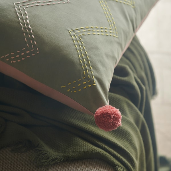 A close-up of MOAKAJSA cushion cover showing pink and yellow embroidery on the green side and a pink pompom in the corner.