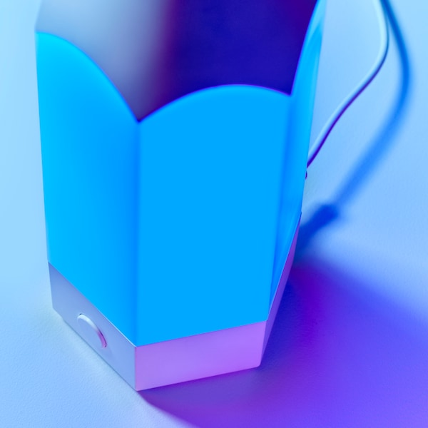 A close-up of PELARBOJ table lamp made in a playful pencil design, showing blue light coming from it.