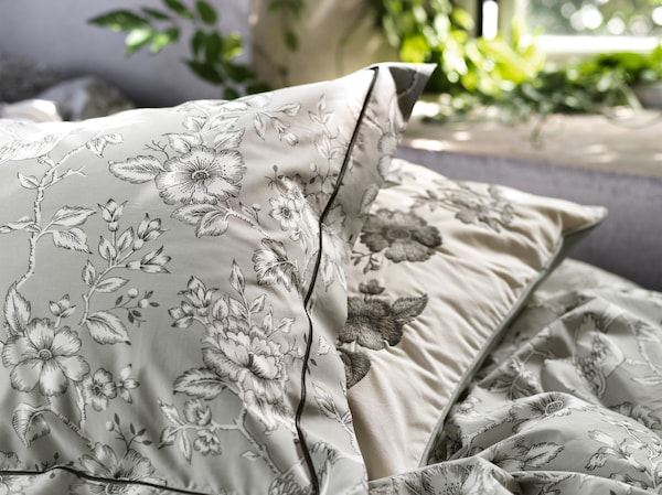 A close-up of PRAKTBRÄCKA quilt cover and pillowcase in grey featuring traditional floral patterns in black and white.