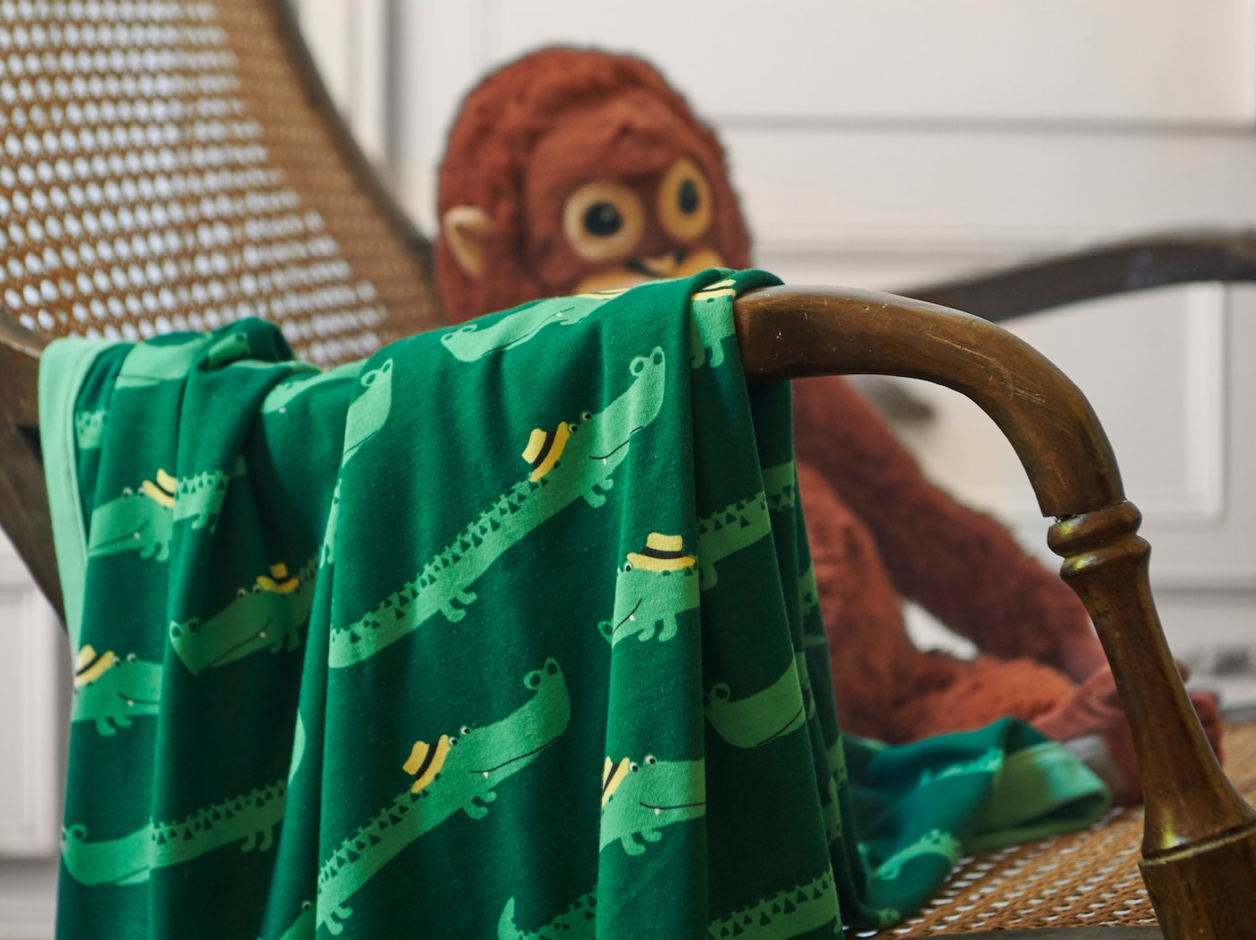 A close-up of RÖRANDE blanket with friendly crocodiles crawling across the green background, placed over a wicker chair.