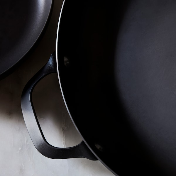 A close-up of the black carbon steel VARDAGEN frying pan with a handle placed on a grey marble countertop.