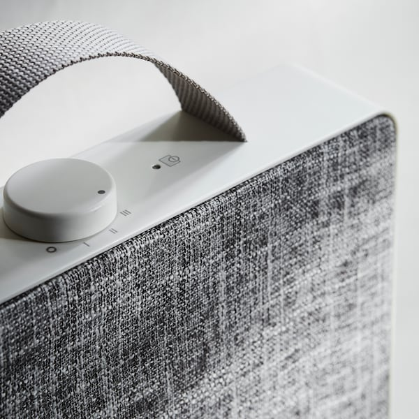 A close-up of the control knob and handle of a white FÖRNUFTIG air purifier with a grey textile side.