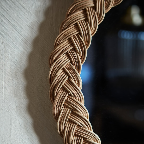 A close-up of the edge of KRISTINELUND mirror made in decoratively woven rattan, hanging on a grey wall.