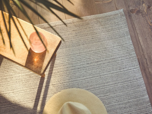 A close-up of the flatwoven TIPHEDE rug with a side table and Panama hat placed on it, while sunlight streams in on one side.