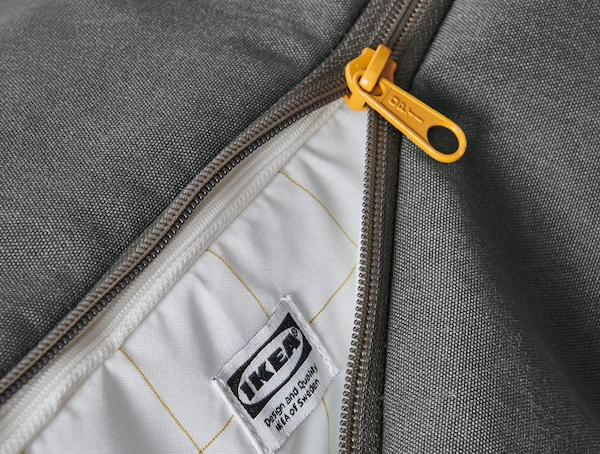 A close-up of the green DRÖMSÄCK backpack's zip and inside fabric.