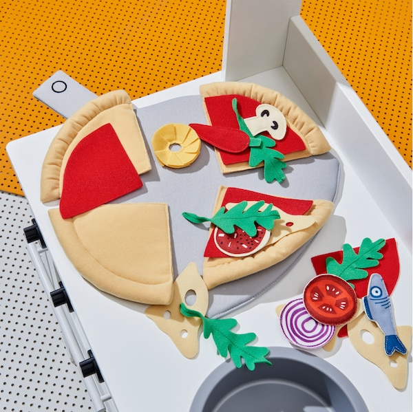 A close-up of the many play pieces included in DUKTIG 24-piece pizza set such as tomato, fish and onion.