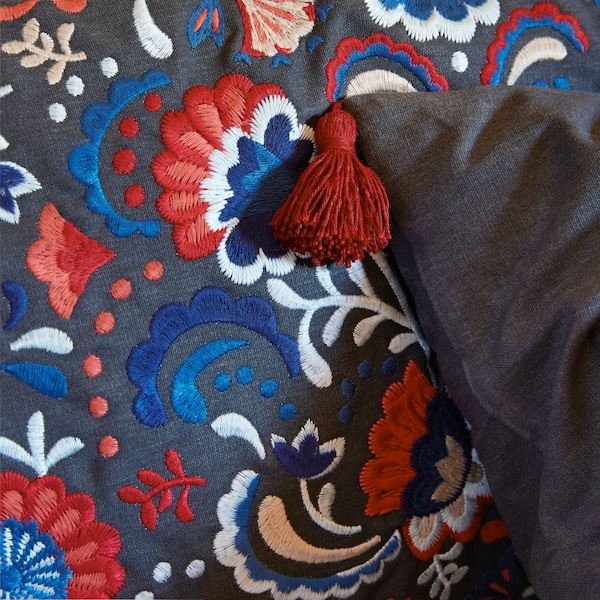 A close-up of the traditional-styled floral embroidery of SKOGSKORN cushion with tassels in the corners.