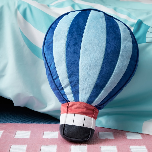 A close-up of UPPTÅG cushion made in the shape of a hot air balloon in blue, made of recycled polyester.
