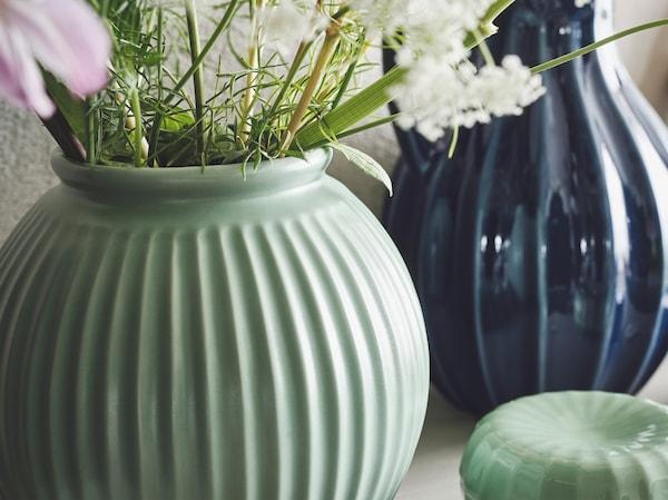 A close-up on a light green VANLIGEN vase with fresh spring flowers and a blue VANLIGEN vase/jug in the background.