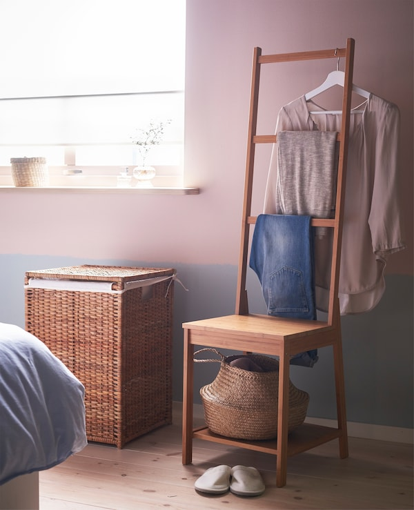 A clothes corner with a chair and basket for wear-again clothes and a laundry bin for dirty clothes.
